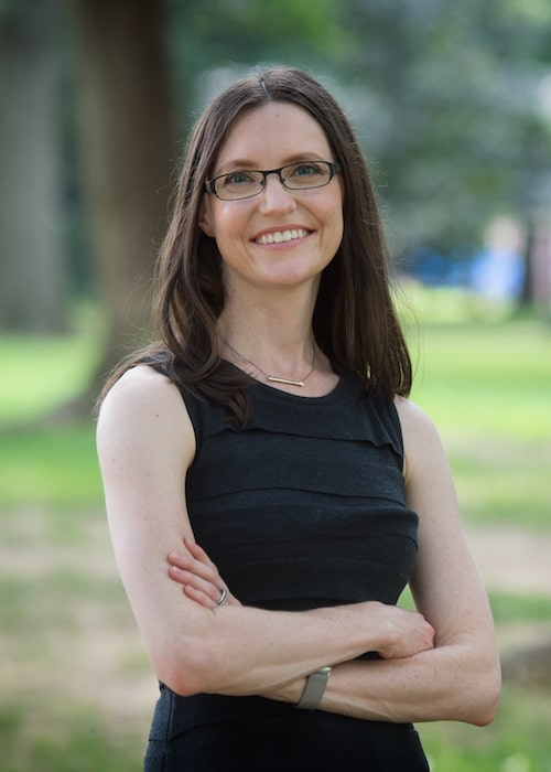 Dr. Amanda Romsa Polack smiling and folding her arms in a park